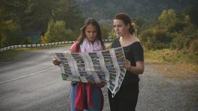 Two tourists are looking for a road, studying the map of Altai during the trip. Slow motion stock footage
