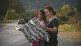 Two tourists are looking for a road, studying the map of Altai during the trip. Slow motion stock video