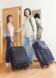 Two tourists with luggage near door Royalty Free Stock Photography