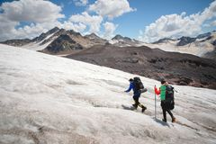 Two tourists, a man and a woman with backpacks and crampons on their feet walk along the glacier against the background. Two tourists, a men and a women with stock photos