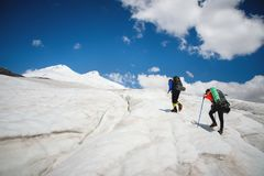 Two tourists, a man and a woman with backpacks and crampons on their feet walk along the glacier against the background. Of the mountain Elbrus and the sky and royalty free stock images