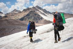 Two tourists, a man and a woman with backpacks and crampons on their feet walk along the glacier against the background. Two tourists, a men and a women with royalty free stock image