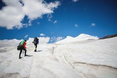 Two tourists, a man and a woman with backpacks and crampons on their feet walk along the glacier against the background. Two tourists, a men and a women with stock images
