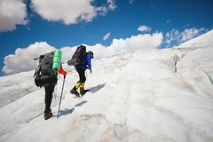 Two tourists, a man and a woman with backpacks and crampons on their feet walk along the glacier against the background. Two tourists, a men and a women with royalty free stock photos