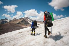 Two tourists, a man and a woman with backpacks and crampons on their feet walk along the glacier against the background. Of the mountains of the sky and clouds stock photos