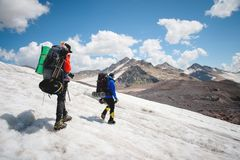 Two tourists, a man and a woman with backpacks and crampons on their feet walk along the glacier against the background. Of the mountains of the sky and clouds stock images