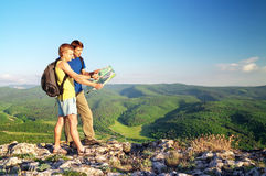 Two tourists in mountain read the map. Royalty Free Stock Images