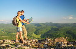 Two tourists on mountain read the map. Royalty Free Stock Image