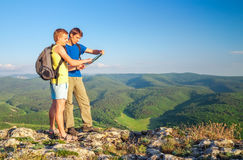 Two tourists on mountain read the map. Mens on top of cliff. Tourism concept Stock Photos