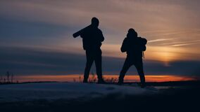 Two tourists photographer man silhouette of sunlight nature landscape winter snow. two male photographers travel the man. Two tourists photographer man stock footage