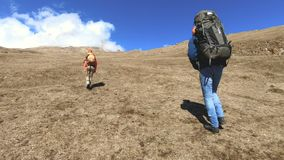 Two tourists photographers with backpacks in hats and sunglasses go up the hill on the yellow grass with cameras in stock footage