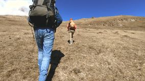 Two tourists photographers with backpacks in hats and sunglasses go up the hill on the yellow grass with cameras in stock video footage