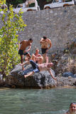 Two tourists pushed his friend in a mountain stream. Stock Image
