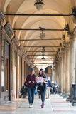 Two tourists read the map of the city. Couple of friends in holiday in Bologna read the map of the city by walking under the arcades Stock Photography