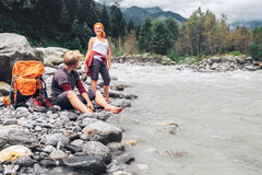 Two tourists refresh near the mountain river Stock Photo