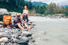 Two tourists refresh near the mountain river Stock Images