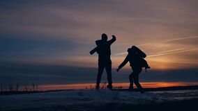 Two tourists run at sunset jumping silhouette funny positive nature landscape winter snow. two male photographers stock video