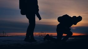 Two tourists run at sunset silhouette and fall funny positive nature landscape winter snow. two male photographers stock video