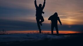 Two tourists run at sunset silhouette funny positive nature landscape winter snow. two male photographers lifestyle man stock footage