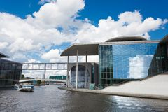 Two tourists ships floats on the river Spree next to a modern buildings of Bundestag and Marie-Luders-Haus. Berlin - Germany Stock Photo