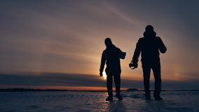 Two tourists silhouette men go to sunset travelers. tourism concept two people outdoors photographers walking through. Two tourists silhouette men go sunset stock video footage