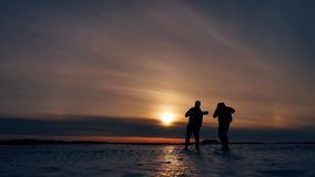 Two tourists silhouette men go to sunset travelers. tourism concept two people photographers walking through the snow. Two tourists silhouette men go sunset stock video
