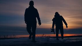 Two tourists silhouette men go to sunset travelers. tourism concept two people photographers walking through the snow. Two tourists silhouette men go sunset stock video footage