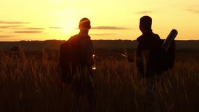 Two tourists silhouettes. two tourists at sunset are standing in the field watching cards in the smartphone. tourists. Drink water silhouette nature from stock video footage