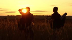 Two tourists silhouettes. two tourists at sunset are standing in the field watching cards in the smartphone. tourists. Drink water silhouette from nature stock video footage