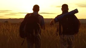 Two tourists silhouettes. two tourists go at sunset. tourist nature silhouette slow motion video nature. Two tourists silhouettes. two tourists go sunset stock footage