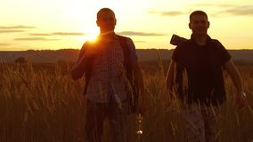 Two tourists silhouettes. Two tourists nature go at sunset. Tourist silhouette nature slow motion video. Two tourists silhouettes. Two tourists nature go sunset stock video footage