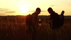 Two tourists silhouettes. two tourists at sunset are standing in the field watching cards in the smartphone. tourists. Drink water from plastic bottle slow stock footage