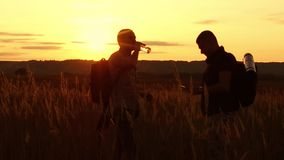 Two tourists silhouettes. Two tourists at sunset are standing in the field watching cards in the smartphone. Tourists drink water silhouette from nature stock video footage