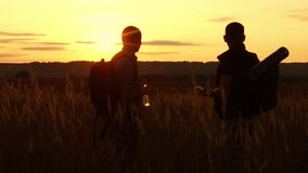 Two tourists silhouettes. Two tourists at sunset are standing in the field watching cards in the smartphone. Tourists. Drink water nature silhouette from stock video footage