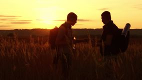 Two tourists silhouettes. two tourists at sunset are standing in the field watching cards in the smartphone. tourists. Drink water silhouette from plastic stock video footage