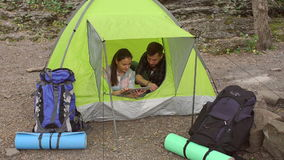 Two tourists sitting in the tent with the tablet. stock video footage