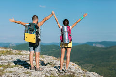 Two tourists stand on the mountain. And raise your hands up Stock Images