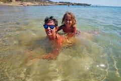 Two tourists take a bath in Farangas beach, Paros. Greece kayak faragas cyclades island boats greek sea mediterranean summer azure cycladic nature travel rocky stock image