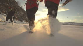Two tourists and travelers on the ice of Lake Baikal. A guy and a girl are walking and running on snow-covered ice. The camera looks at his feet. Between them stock video