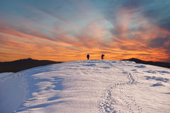 Two tourists walk on a mountain slope to the summit against the backdrop of mystical clouds at sunset Stock Images