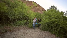 Two tourists walk along a trail in the mountains. Two tourists walk on a rocky trail in the mountains with large backpacks stock footage