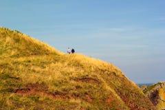 Two tourists walking along beautiful Cliffs of Scotland, St Abb`s Head, UK. Two tourists walking along beautiful Cliffs of Scotland in St Abb`s Head, UK Stock Photos