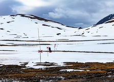 Two tourists walking a snowy mountain path to a passage. Two tourists walking a through a snow field in mountains towards a small cottage in a distant passage Royalty Free Stock Photo