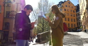 Two Tourists Walking in Stockholm. Steadicam shot of two tourists on the street of Stockholm, Sweden. Woman is taking photos of buildings with tablet PC, man is stock footage