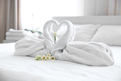 Two towel swans and flowers. On white bedding Stock Photo