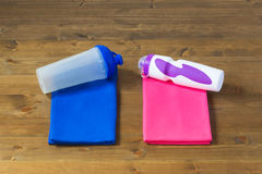 Two towels and a bottle for fitness men and women. On a pink and blue towel lie bottles for sports nutrition Stock Photos