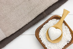 Two towels with bowl filled with white bath salt and wooden spoo Stock Image