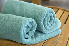 Two towels braided in a tubule on chair. Two towels  braided ore curtailed in a tubule on the wood chair Royalty Free Stock Image