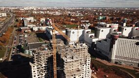 Two tower crane working on a walls. Construction of apartment building in big city center. Autumn cloudy day. Aerial shot. 4K stock video