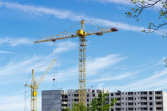 Two tower cranes against of multi-story residential building con Stock Photos